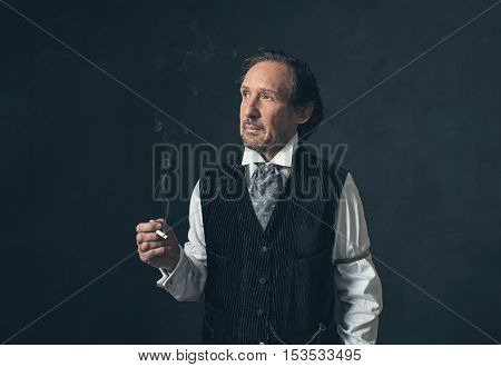Mature Man With Beard And Cigarette In Vintage 1900 Western Clothing.