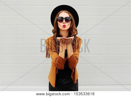 Fashion Portrait Woman Blowing Red Lips Sends Air Sweet Kiss Wearing Black Hat, Sunglasses, Jacket O