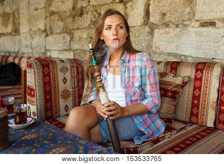 Beautiful young woman smoking a hookah and drinking tea in a cafe Istanbul Turkey