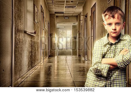 Boy standing in a corridor leaning his shoulder against the wall. Surrealism.