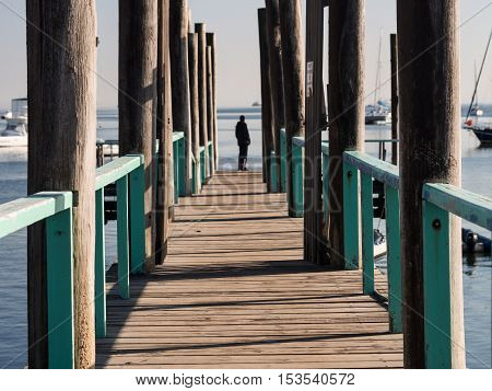 WALVIS BAY NAMIBIA - JUNE 22 2016: Person standing at the end of a bridge in the port in Walvis Bay Namibia.