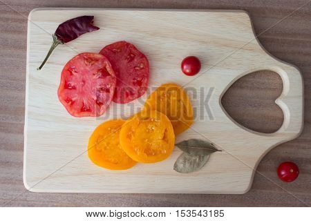 carving bord with red and yellow tomato