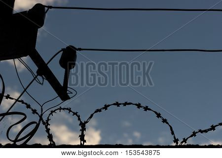 silhouette of a birbed wire and a wire