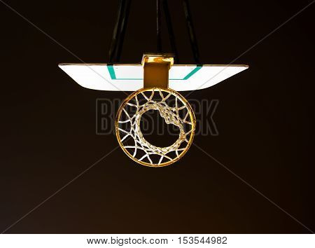 Looking up from the bottom of a basketball net and backboard lit up against a black background