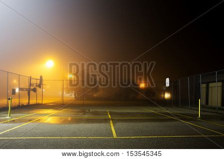 A fenced tennis and basketball court at school yard on a foggy night under street lights