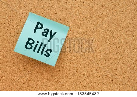 A reminder to pay your bills Bulletin board with a blue sticky note with text Pay Bills