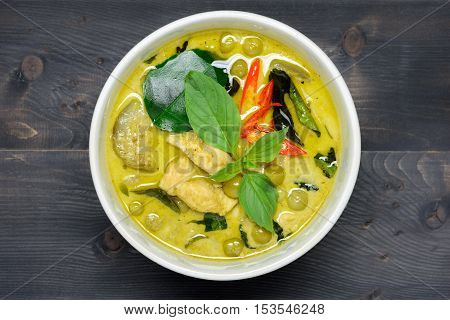 green curry with chicken (Kang Keaw Wan Gai) on wooden background top view Thai local food