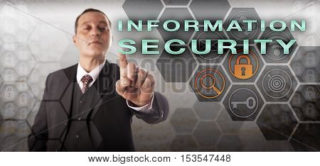 Self-assured male cyberspace inspector pressing INFORMATION SECURITY onscreen. Information technology concept for InfoSec computer security data security crime prevention and cryptography.
