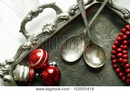 Over head view of an elegant silver serving platter, silver spoons, retro Christmas ornaments and a strand of red tree trimming beads.