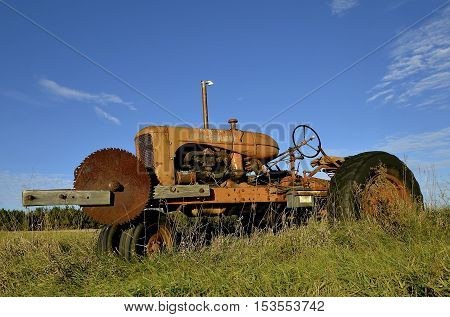 GARFIELD, MINNESOTA, October 21, 2016:  The tractor with an attached saw blade is an Allis Chalmersllis-Chalmers, a U.S. manufacturer of machinery for various industries includung agricultural equipment, construction, power generation, and power transmiss