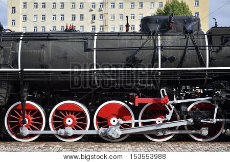 Red wheels of old black steam locomotive. Wheels of an old soviet steam train