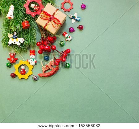 Christmas or New Year background: wooden toys, fur-tree, gifts, decoration on green background