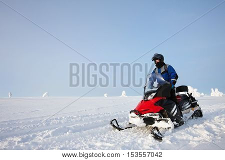 Man driving snowmobile in snowyfield in a sunny day. Lapland, Finland.