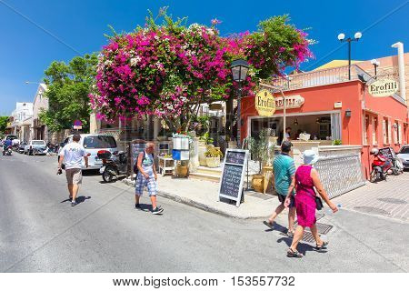 Rethymnon, Island Crete, Greece - July 1 2016: People and tourists walking on the street of Rethymnon near the cozy Cretan cafe with ad on the black board