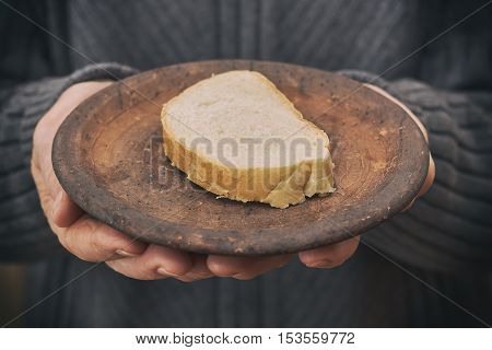 Old man's hands holding rustic plate with one slice of bread. Concept image for poverty.