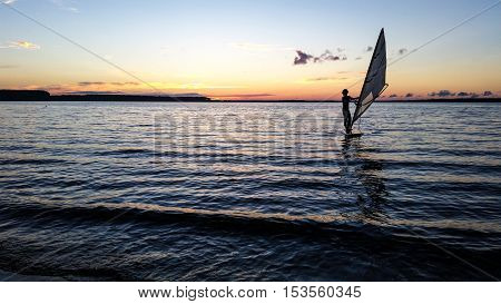 Windsurfer Sailing In The Lake At Sunset. Extreme Water Sport.