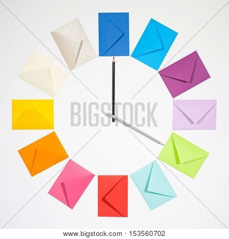Twelve envelopes isolated on white background. Clock of colored envelopes for Christmas mailing.