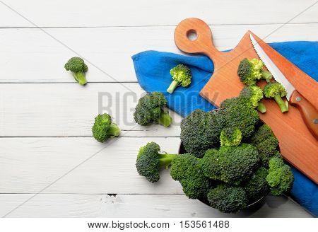 Brocolli On The Cutting Board With Wet Knife On The White Wooden Table.top View.copy Space