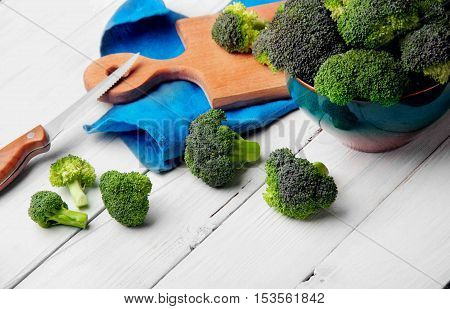 Brocolli On The Cutting Board With Knife On The White Wooden Table.copy Space