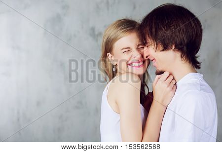 happy young couple hugging and kissing, against studio background