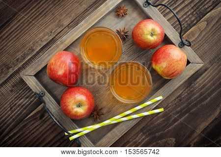 Apple cider in glass with fresh apples on wooden background top view