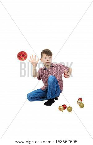 Boy throwing a Christmas tree ball. Isolated on white background.