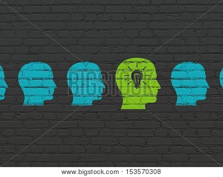 Finance concept: row of Painted blue head icons around green head with light bulb icon on Black Brick wall background