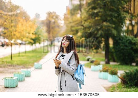 portrait of young brunnette woman outdoors in a park in autumn listening to music with headphones.