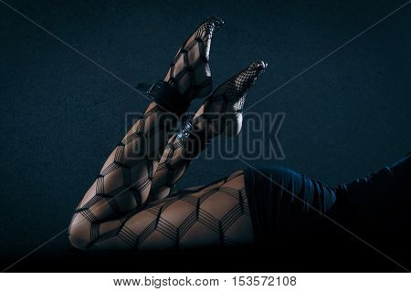 Low key special toned photo of sexy female nude legs in net tights and body in black dress against dark background horizontal view