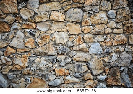 Background of grey and brown stonework wall with different shapes and forms stones and rough texture
