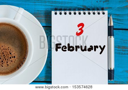 February 3rd. Day 3 of month, calendar in notepad on wooden background near morning cup with coffee. Winter time. Empty space for text.