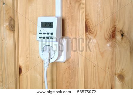 Working plugged white electric timer power socket operated smart house system against wooden wall inside room side view closeup
