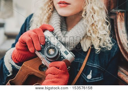 Old film camera in the hands of a young blond curly female in warm red gloves winter