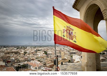 Spanish flag fluttering over Cox town, Alicante, Spain