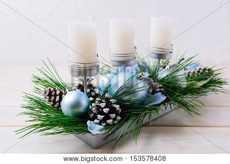 Christmas table centerpiece with candles and blue ornaments. Christmas decoration with blue balls. Christmas party background.