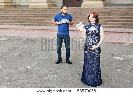 Funny image. Сouple expecting a baby girl: man holds a sign saying