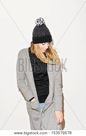 Closeup studio portrait of fashionable young blonde Caucasian woman in long gray cardigan, black turtleneck, knitted beanie hat, posing against white wall. Studio lighting, no retouch.