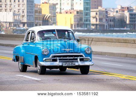 HAVANA,CUBA - OCTOBER 25,2016 : Old american car at the famous seaside Malecon avenue in Havana