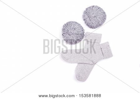 Pair of gray woolen socks and two knitting yarns isolated on white background