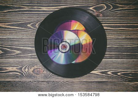 old and morden audio disks on the wooden table, selective focus and toned image