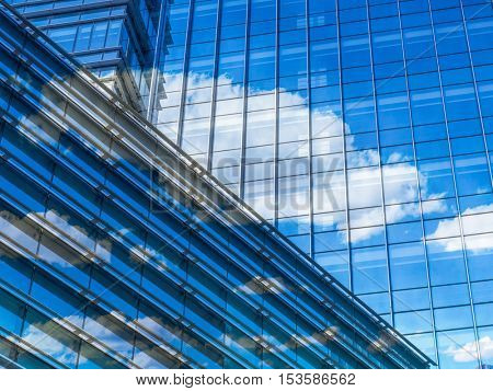 modern glass building with clouds and sky reflections.