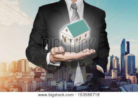 Realtor businessman with home model on hand, with urban city view in sunrise background