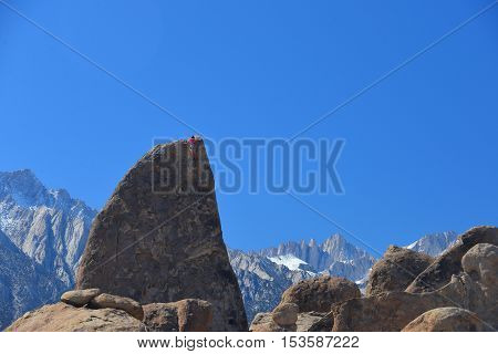 climber on sharks fin arete route with mount whitney in back ground at alabama hills california