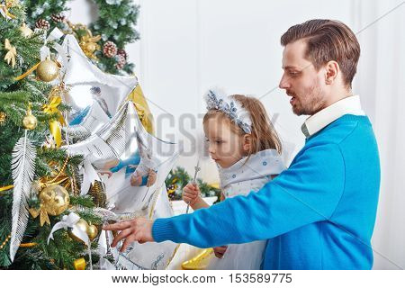 Daughter and father decorate the Christmas tree. Father supports daughter and little cute girl hangs on the Christmas tree toys. The festive mood. Family celebration.