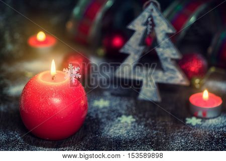 Christmas composition with red candles festive decorations on old wooden background. Rustic stile