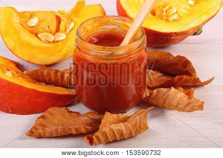 Sauce Of Pumpkin In Glass Jar And Autumnal Leaves On Wooden Table