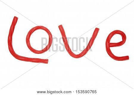 love for sweets. the inscription love is laid out from the red twisted licorice candy. isolated on a white background