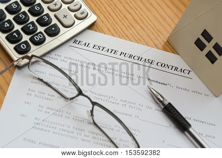 real estate purchase contact with an architectural model and a calculator