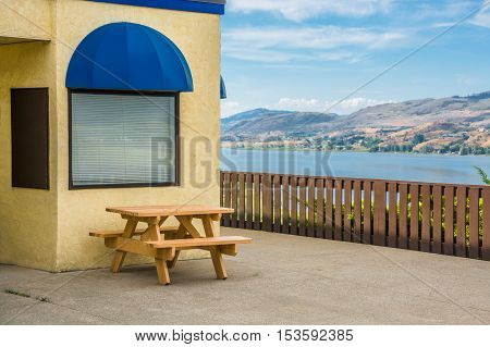 Cafe area with wooden table on Okanagan lake shore. Table and benches at rest area with mountains and cloudy sky background.