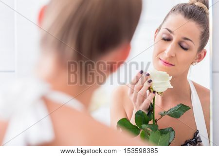 Happily smiling woman holding a white rose and regarding herself in the bathroom mirror